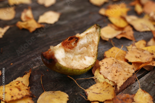 Valokuva  A quarter of a flaccid apple slice on a wooden table with yellow birch foliage