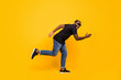 Bargains i come. Full length profile side photo of funky crazy afro american guy go walk run fast incredibles sales scream wear modern clothing isolated over yellow color background