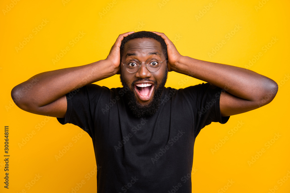 Fototapeta Photo of cheerful positive funny cute black man overjoyed about discounted shopping mall grabbing his head with hands in t-shirt isolated vibrant color yellow background