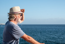 A Senior Man With White Beard And Hair Looking Far Away At The Sea From The Cliff. Horizon Over Water. Blue Sky And Ocean On Background