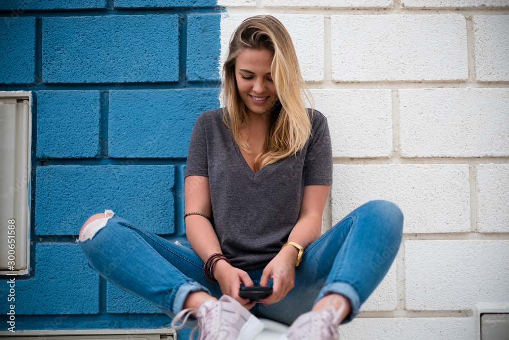 Fototapeta woman with blue and white wall at the background sitting on a wall using her phone and surfing on the network - social network