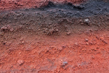 A Cut Of Soil With Rocks And Red Soil