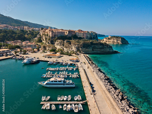 Montage in der Fensternische Blau türkis Aerial view of boats moored at the Port of Tropea, Calabria, Italy. Houses overlooking the sea. Beach and Sanctuary on the horizon. Italian coasts