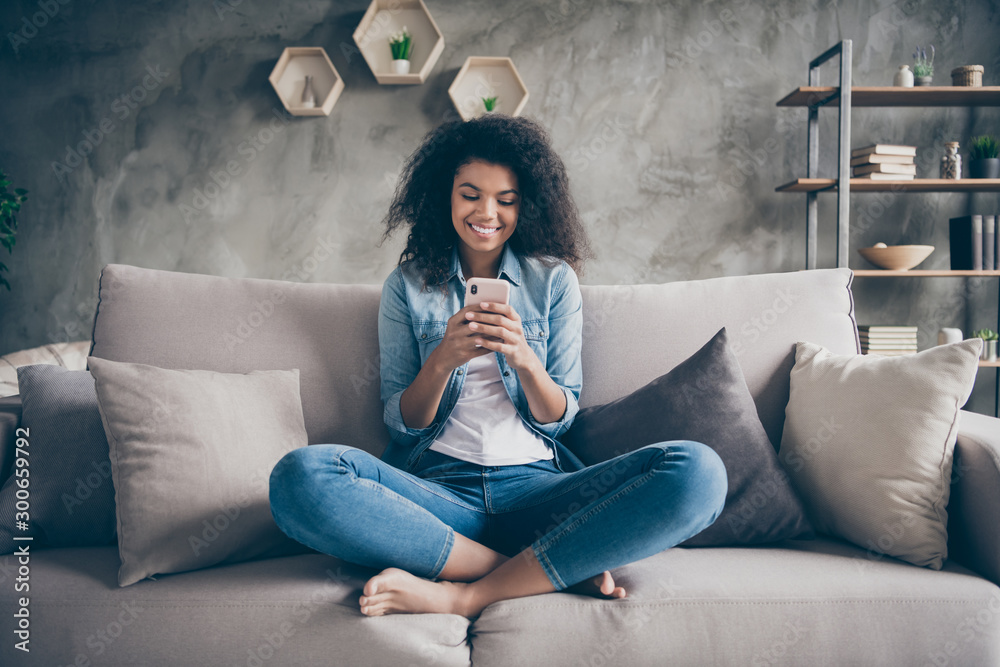 Fototapety, obrazy: Photo of pretty dark skin curly lady homey domestic texting telephone with friends reading instagram comments sitting comfy couch casual denim outfit living room indoors
