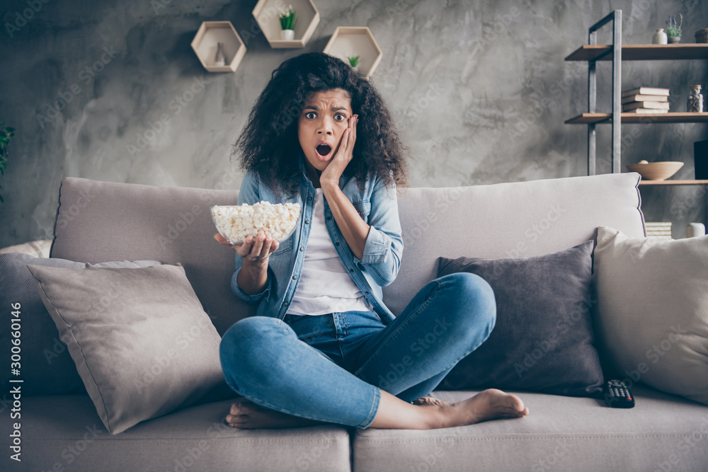 Fototapety, obrazy: Photo of pretty dark skin wavy lady homey mood eating popcorn watching television horror show hand on cheek sitting cozy couch casual jeans outfit flat indoors