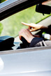 Man driving car and woman shows him direction. Inside car on men hands on steering wheel.