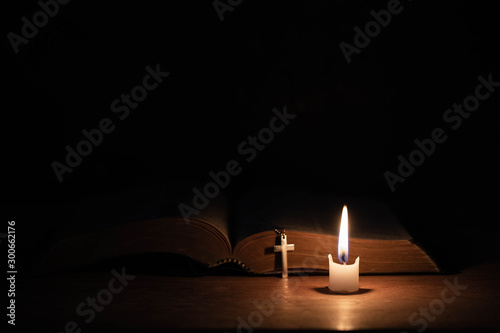 Fotografie, Obraz  Cross with bible and candle on a old oak wooden table.