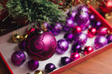 A Large Purple Decorated Christmas Ball On A Branch Of A New Year's Eve Against The Background Of Other Colored Decorations. Selective Focus.