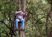 Hunter In Tree Stand Taking Aim At His Game In Hopes Of A Successful Hunt