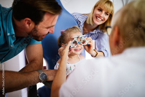 Fotografía  Ophthalmologist is checking the eye vision of little cute girl in modern clinic