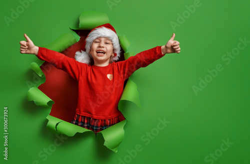 girl in Santa hat on color background