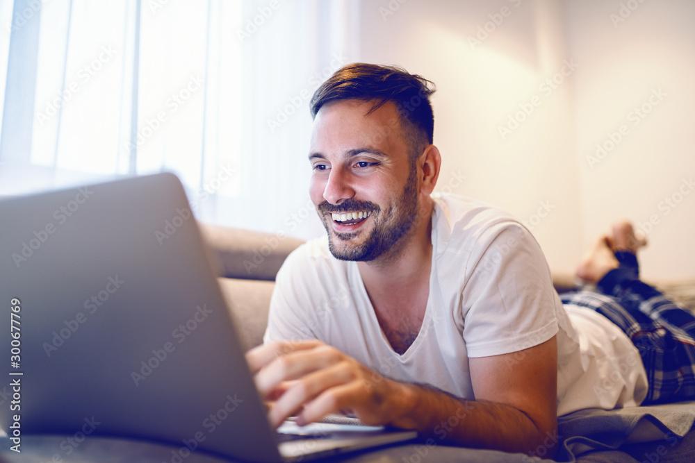 Fototapeta Joyful caucasian man in pajamas lying on stomach on sofa in living room and surfing on internet.