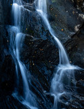 close up shot of a waterfall in the argyll region of the highlands of scotland in autumn showing bright water flowing over dark black rock