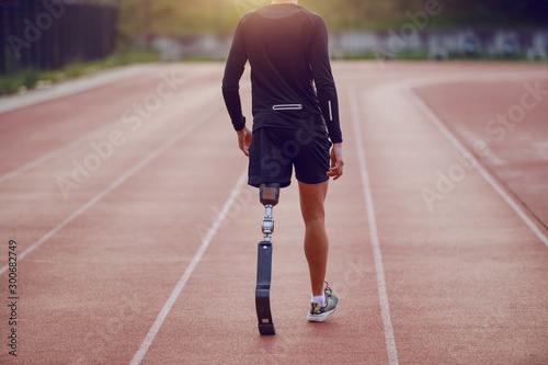 Cuadros en Lienzo Rear view of handsome caucasian handicapped young man with artificial leg and dressed in shorts and sweatshirt walking on racetrack
