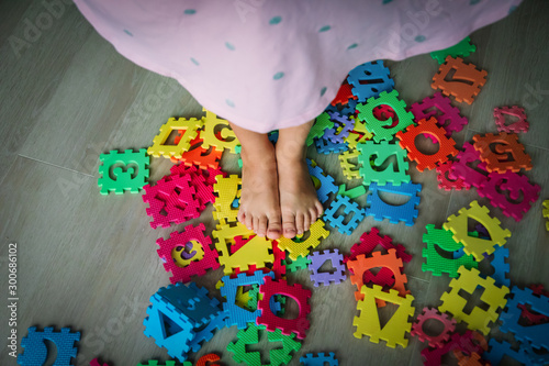too much toy , little girl steps on puzzle trying to go through