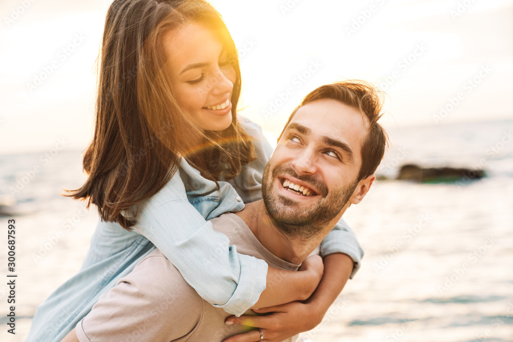 Fototapety, obrazy: Image of young man giving piggyback ride and looking at beautiful woman