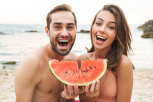 Photo Of Excited Young Couple Holding Piece Of Watermelon And Laughing