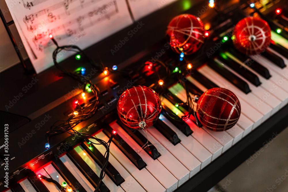 Piano keyboard with Christmas decoration, closeup <span>plik: #300691703 | autor: Angelov</span>
