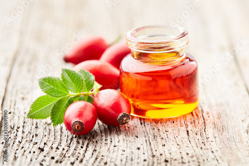 Obraz Rose hips oil with berries on wooden background - fototapety do salonu