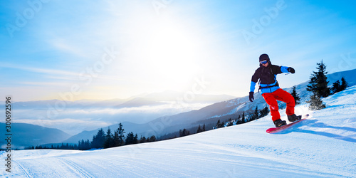 Papiers peints Glisse hiver Snowboarder Riding Red Snowboard in Mountains at Sunny Day. Snowboarding and Winter Sports