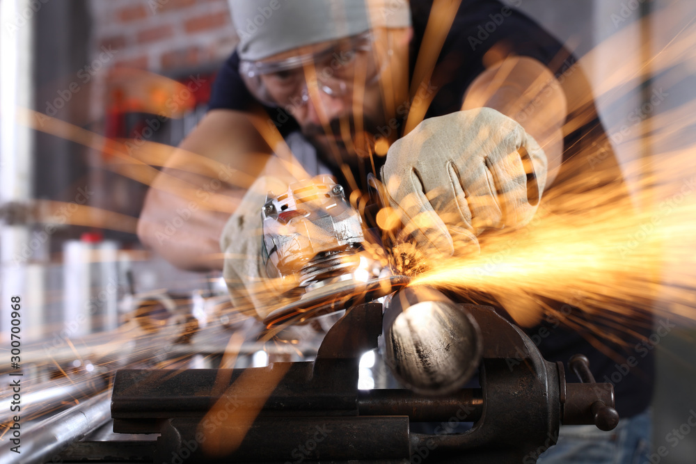 Fototapety, obrazy: man work in home workshop garage with angle grinder, goggles and construction gloves, sanding metal makes sparks closeup, diy and craft concept