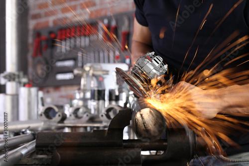 Photo hands man work in home workshop garage with angle grinder, sanding metal makes s