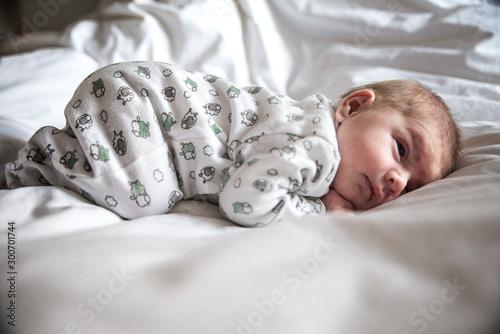 adorable bebé durmiendo en la cama entre sábanas blancas Wallpaper Mural