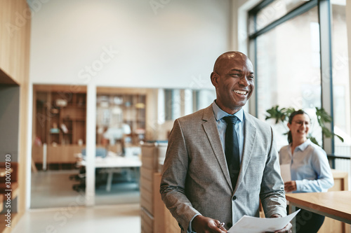 African American businessman laughing while walking through a mo