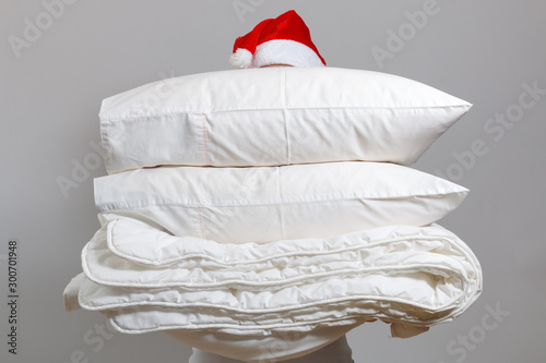 Fotomural  Woman in santa hat holding a warm duvet and feather pillows against a gray wall