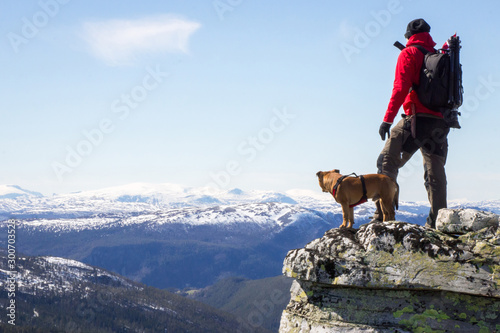 Man and dog standing on steep hillside and looking towards the snowy peaks of Jotunheimen in Norway Canvas Print