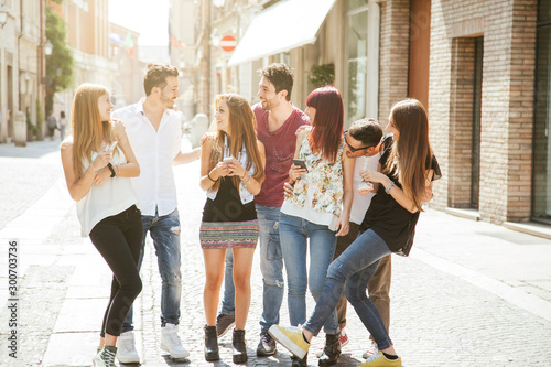 Millennials having fun together in the city - Seven people walking on the street Canvas Print