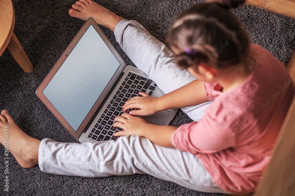 Fototapety, obrazy: Young smart baby girl playing at home and using laptop.