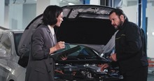 In A Modern Service Auto Old Mechanic Guy With A Office Manager Lady In A Suit Have A Conversation They Look Over The Car To Find The Problem And To Notes On The Map