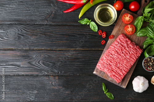 Flat lay composition with fresh raw minced meat on black wooden table Canvas Print