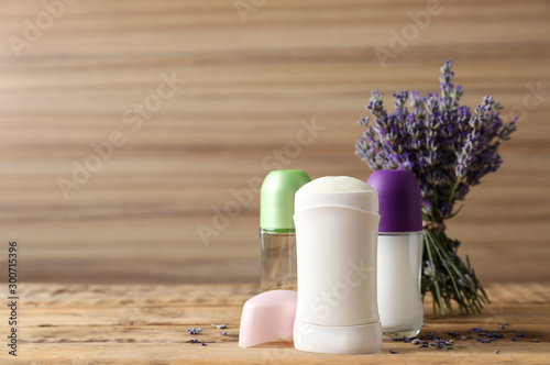 Different female deodorants and lavender flowers on wooden background, space for Canvas Print