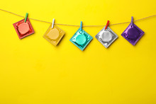 Colorful Condoms Hanging On Clothesline Against Yellow Background, Space For Text. Safe Sex Concept
