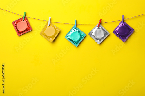 Cuadros en Lienzo  Colorful condoms hanging on clothesline against yellow background, space for text