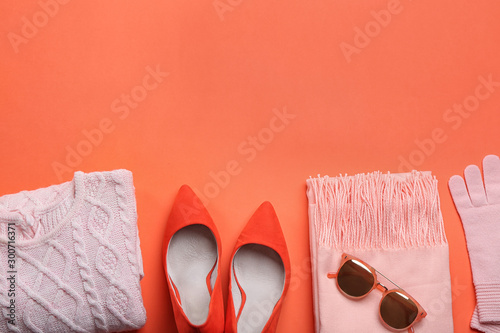 Slika na platnu Flat lay composition with warm clothes on coral background