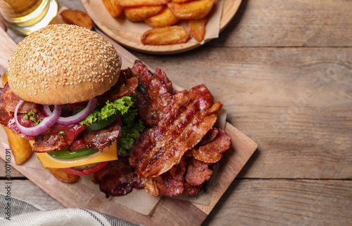 obraz PCV Composition with juicy bacon burger on wooden table, above view. Space for text
