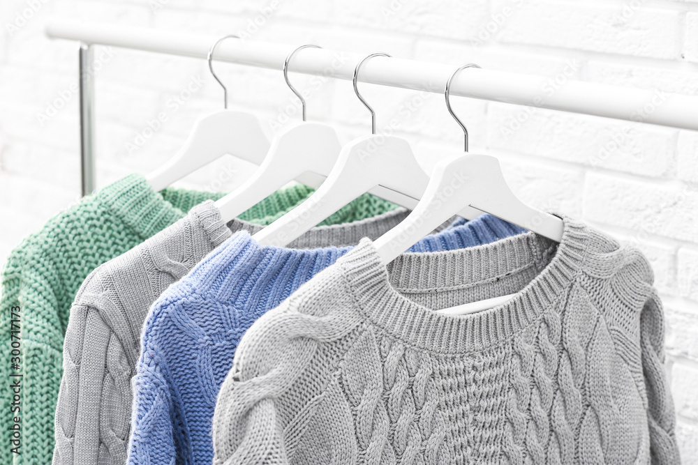 Fototapety, obrazy: Collection of warm sweaters hanging on rack near brick wall, closeup