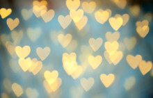 Blurred View Of Beautiful Gold Heart Shaped Lights On Light Blue Background