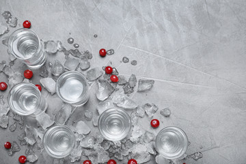 Shots of vodka, cranberries and ice on grey background, flat lay. Space for text