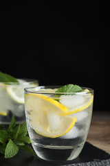 Glass of cocktail with vodka, ice and lemon on wooden table against black background. Space for text