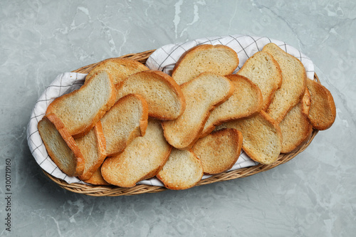 Fotografie, Obraz  Basket with toasted bread on grey table, top view