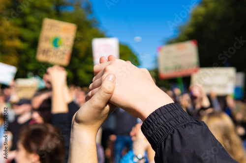 two young people at a rally, joining hands together signaling peace, unity and d Canvas Print