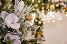 A Beautiful Christmas Bouquet Of Fir Branches With Colorful Balls And Flowers, A Garland Stands In The Living Room. Photo In Warm Tint.