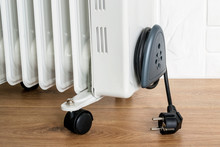Home Electric Oil Heater On Plastic Twin Wheels And With Cable Reeled Up On A Cable Storage. White Oil-filled Radiator On A Brown Wooden Floor.