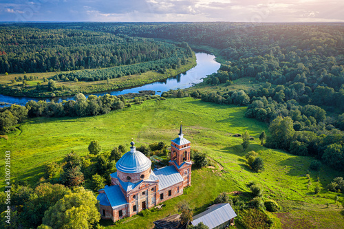 Staande foto Oude gebouw Ancient stone Orthodox Russian church, river bend, green forests and sunset.