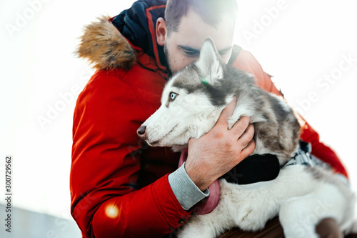 Man hugging Siberian Husky dog on a walk in modern park on sunny winter day Canvas Print