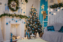 Christmas And New Year Living Room Interior With Decorated Firtree, Fireplace, Blue Candles, Garland Lights, Brown Teddy Bear Toy